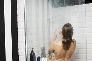 Beautiful naked young woman taking shower in bathroom