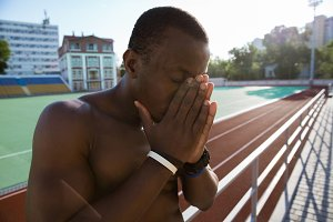 Close up of a tired african sportsman leaning on the railing