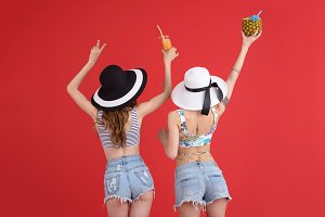 Two women standing isolated over red background drinking cocktails.