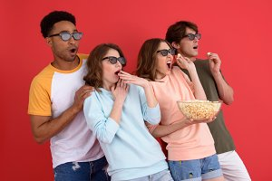 Shocked group of friends watching film eating popcorn.