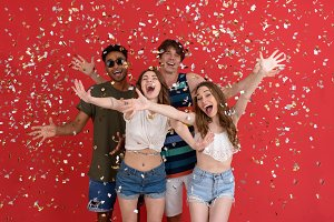 Cheerful group of friends standing isolated over confetti