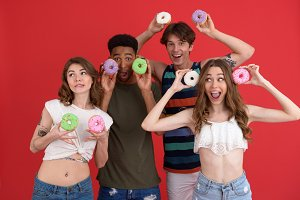 Smiling group of friends friends standing with donuts