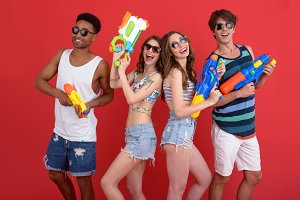 Young group of friends with water toy guns
