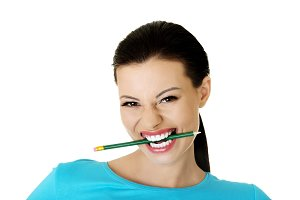 Thoughtful attractive student woman biting pencil