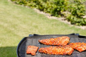 Spareribs on grill with hot marinade