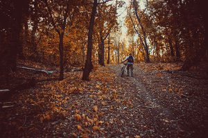 Man with bike in autumn forest