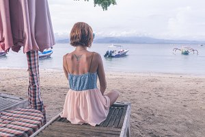 Woman sitting on beach in deck chair on a cloudy day. Nusa Lembongan island, Bali, Indonesia.