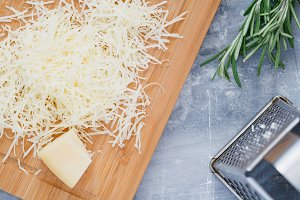 Grated parmesan cheese on a wooden board. Cooking food. Top view.