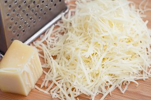 Grated parmesan cheese on a wooden board. Cooking food.