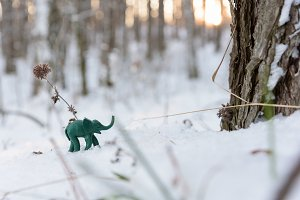 Plasticine green elephant near tree trunk