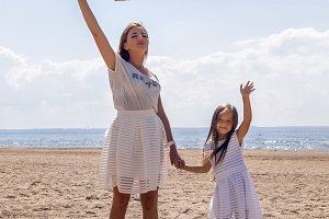 mother and daughter standing on beach with arms