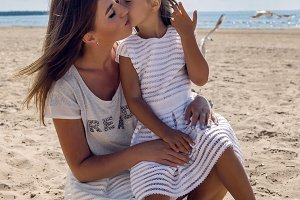 mother holding the daughter sitting on her knees on the beach