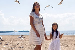 mother and daughter standing on the beach