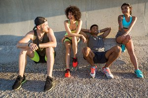 Group of young friends in sportswear resting and talking outdoors