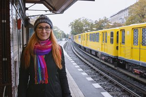 Young hipster woman in glasses and in warmclothes in train station platform