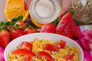 Healthy breakfast cornflakes with milk and fruits
