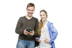 Teen boy and girl standing with mobile phones