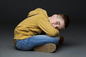 Handsome little boy in jeans sitting on floor