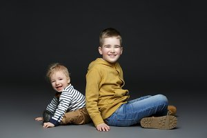 Two brothers in jeans sitting on floor