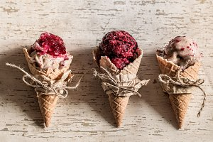 Ice cream waffle cone with berries on wooden background