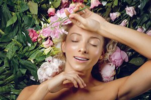 Beautiful girl lying in flowers