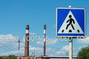 Timelapse, road sign of a pedestrian walkway in the background of a plant with pipes. Urban landscape. Rules of the road, regulation of the automobile flow, traffic of cars. industrial area. Safe passage of pedestrians across the road. Car traffic.