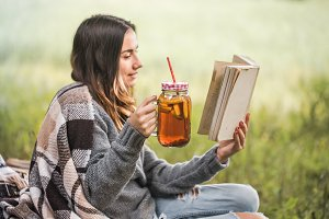 young girl in nature with a drink in hand reading a book