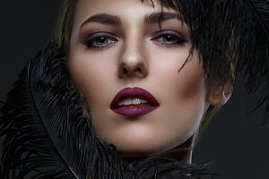 Beautiful girl with black feathers