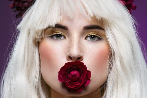 Beautiful girl with rose in mouth