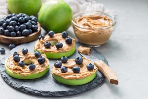 Green apple rounds with peanut butter and blueberries on slate board, horizontal, copy space