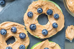 Green apple rounds with peanut butter and blueberries, vertical, top view