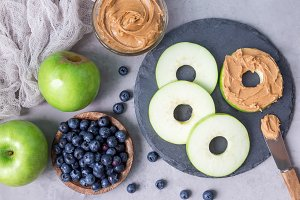 Green apple rounds with peanut butter and blueberries on slate board, horizontal, top view