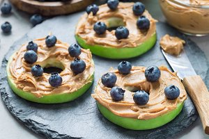 Green apple rounds with peanut butter and blueberries on slate board, horizontal