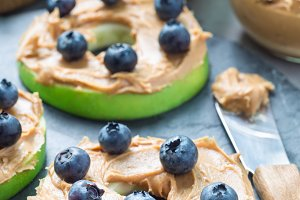 Green apple rounds with peanut butter and blueberries on slate board, vertical