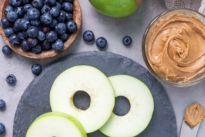 Green apple rounds with peanut butter and blueberries on slate board, vertical, top view