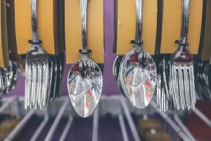 Stainless spoons and fork set hanging in the store. Shopping mall, Bali island, Indonesia.