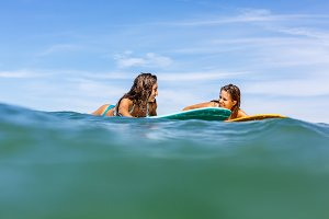 Beautiful girls with surf in sea.