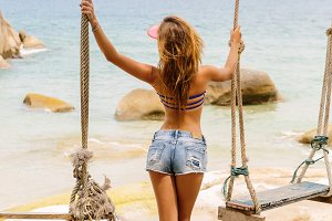 Beautiful girl posing in swings.