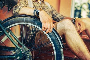 Closeup Hand Of A Young Hipster Man Sitting On Steps Rests On A Bicycle Wheel. The guy rests during a bike trip