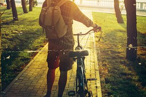 Handsome young man with backpack standing with bike bicycle in summer park at sunset