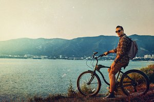Handsome Man Cyclist with a backpack in sunglasses on a bicycle stands on the coast and enjoys the seascape during sunset
