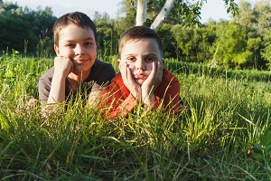 Two boys lies on the green grass in the garden