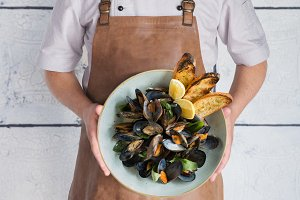Chef keeps a plate with mussels