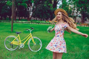 Beautiful blond woman in a straw hat on a lawn with flowers whirls and dances in the park.