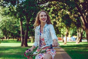 Portrait of happy woman biking in city park on bicycle.