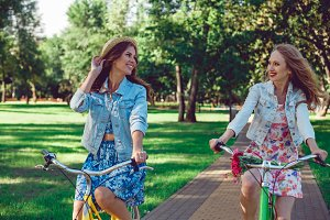Two young female friends riding their bicycles in the park.