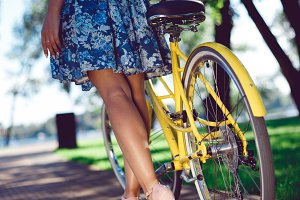 Low section cropped shot female long legs in a dress next to a yellow bicycle
