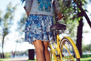 View from the back of a beautiful young woman in a blue dress with an yellow bicycle