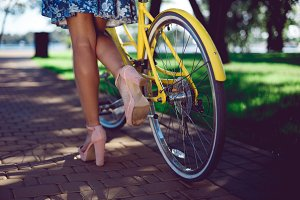 Close-up of female legs in summer boots and yellow bicycle retro wheel