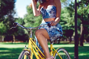 Close up shot of cheerful young female model on bicycle.